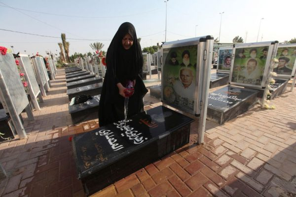 """A woman washes the grave of her relative at the Wadi al-Salam cemetery, Arabic for """"Peace Valley"""", in Najaf, south of Baghdad, Iraq August 5, 2016. REUTERS/Alaa Al-Marjani"""
