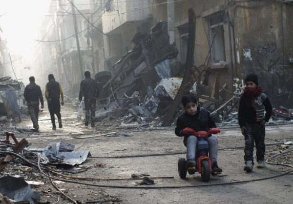 A boy rides on a tricycle along a damaged street in the besieged area of Homs, Syria. REUTERS/Yazan Homsy