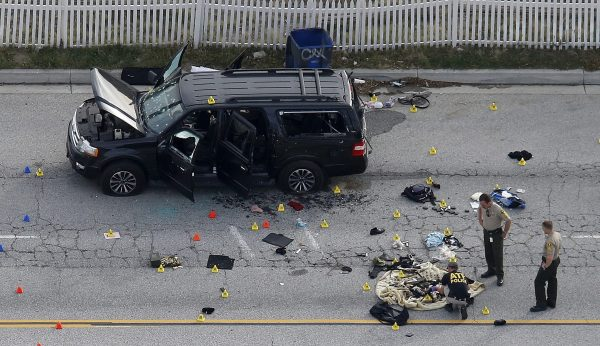 Law enforcement officers look over the evidence near the remains of a SUV involved in the Wednesdays attack is shown in San Bernardino, California December 3, 2015. REUTERS/Mario Anzuoni/File Photo